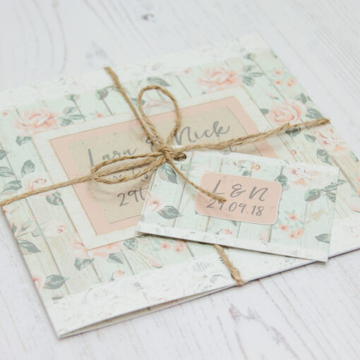 Close up of Folded Apricot Sunrise Wedding Invitations with String & Tag