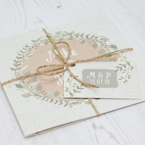 Close up of Folded Botanical Garden Wedding Invitations with String & Tag