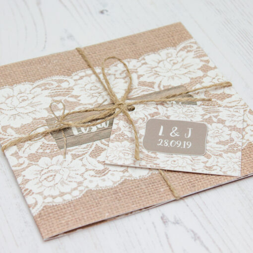 Close up of Folded Chantilly Lace Wedding Invitations with String & Tag