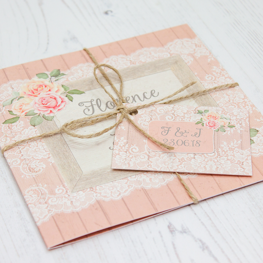 Close up of Folded Coral Haze Wedding Invitations with String & Tag