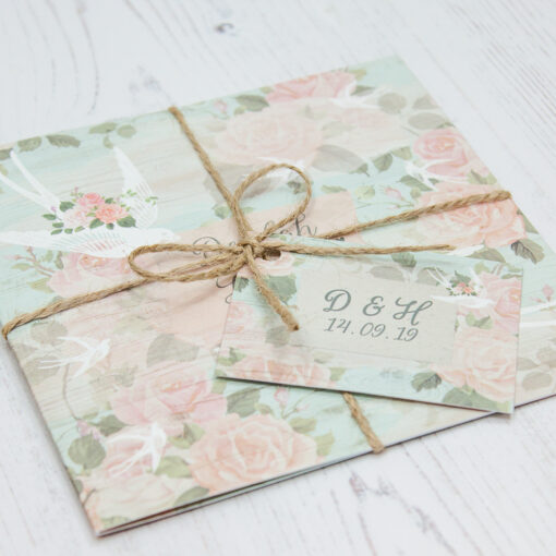 Close up of Folded Dancing Swallows Wedding Invitations with String & Tag