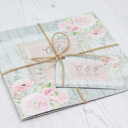 Close up of Folded Dusty Flourish Wedding Invitations with String & Tag
