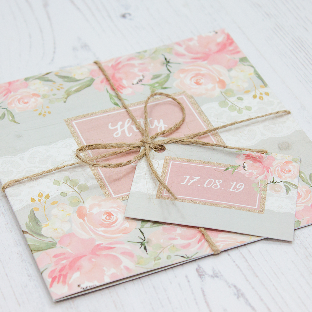 Close up of Folded Enchanted Garden Wedding Invitations with String & Tag