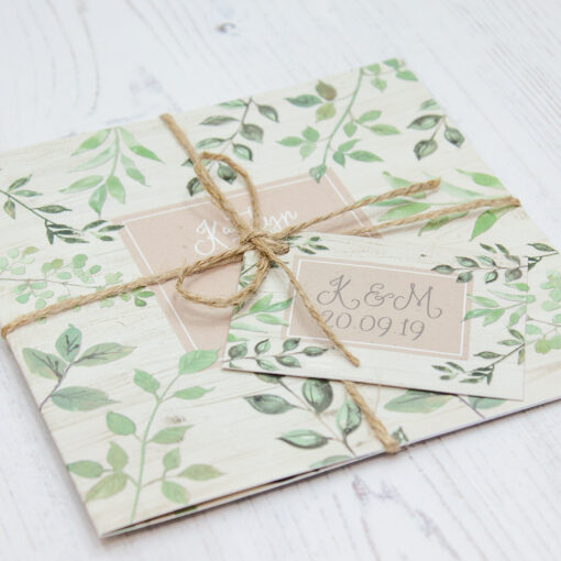 Close up of Folded Evergreen Forest Wedding Invitations with String & Tag