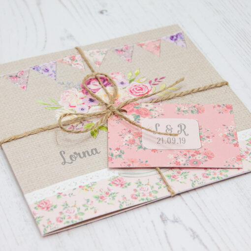 Close up of Folded Floral Blooms Wedding Invitations with String & Tag