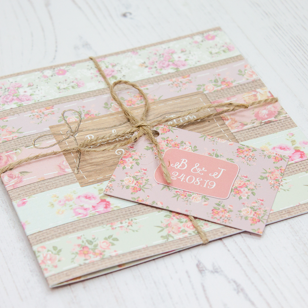 Close up of Folded Floral Furrows Wedding Invitations with String & Tag