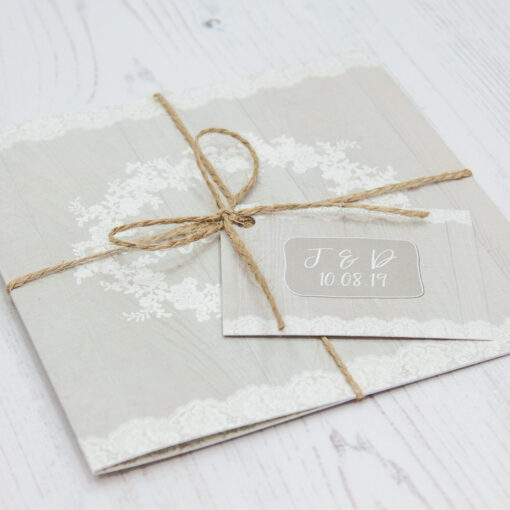 Close up of Folded Grey Whisper Wedding Invitations with String & Tag