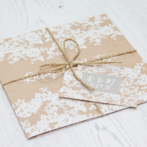 Close up of Folded Lace Filigree Wedding Invitations with String & Tag