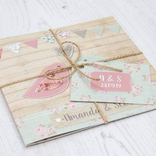 Close up of Folded Lovebirds Wedding Invitations with String & Tag