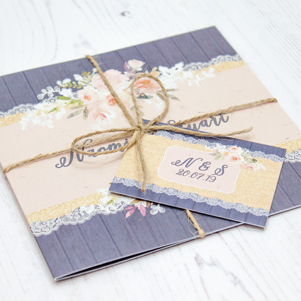 Close up of Folded Midnight Glimmer Wedding Invitations with String & Tag