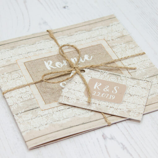 Close up of Folded Natural Elegance Wedding Invitations with String & Tag
