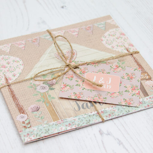 Close up of Folded Rustic Barn Wedding Invitations with String & Tag