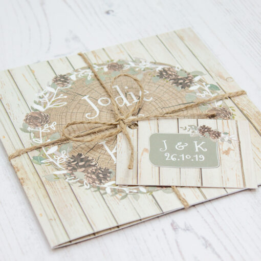 Close up of Folded Wild Woodland Wedding Invitations with String & Tag