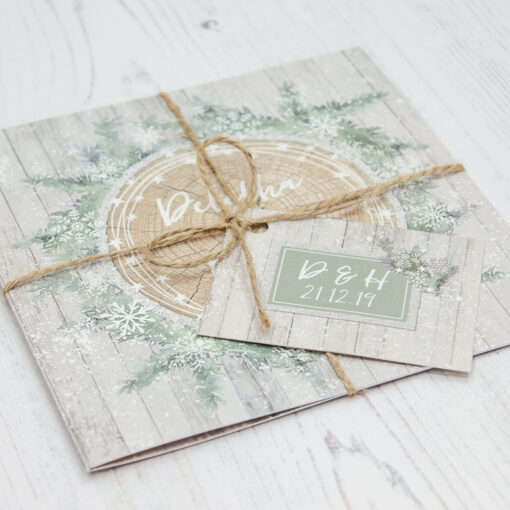 Close up of Folded Winter Wonderland Wedding Invitations with String & Tag