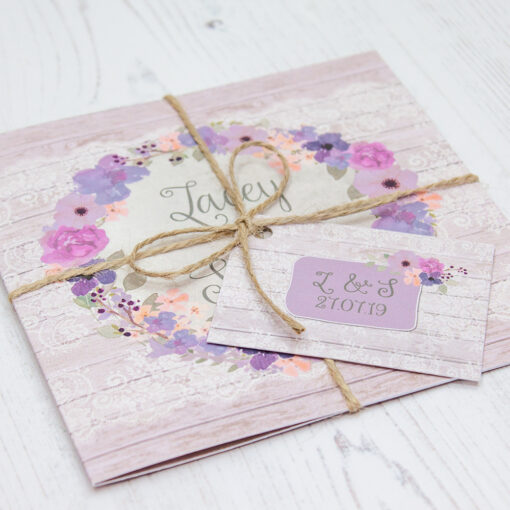 Close up of Folded Wisteria Garden Wedding Invitations with String & Tag
